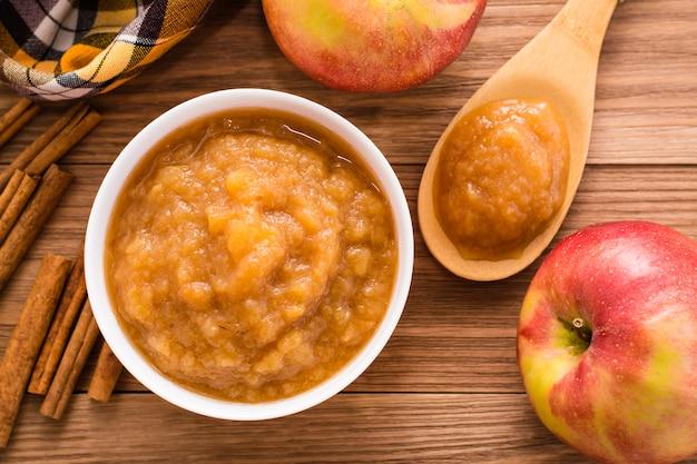 Яблочное пюре, яблоки и корица на деревянном столе, вид сверху