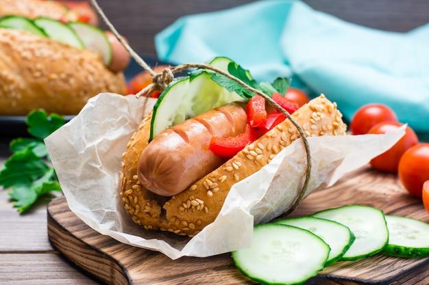 木製テーブルの上のまな板の上にパーチメント紙に包まれた揚げソーセージ、ロールパン、新鮮な野菜から作られた食欲をそそるホットドッグ。閉じる