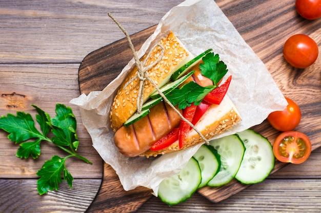 木製テーブルの上のまな板の上にパーチメント紙に包まれた揚げソーセージ、ロールパン、新鮮な野菜から作られた食欲をそそるホットドッグ
