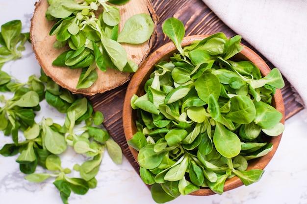 レタスの葉は木製のボウルとテーブルの上に、トップビュー