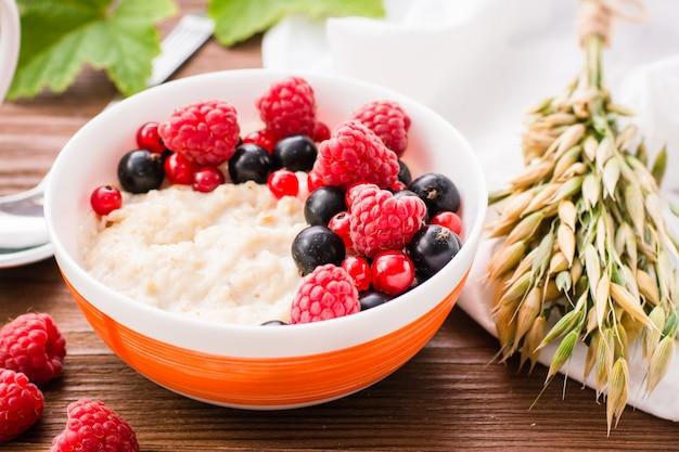 Крупный план овсяной каши и свежих ягод в миску