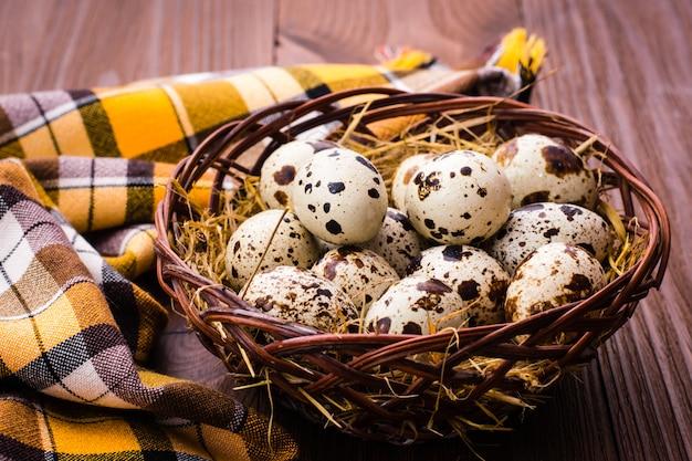 Корзина с перепелиными яйцами и салфеткой на деревянном столе