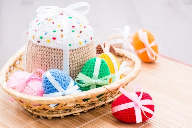 Вязаные пасхальные яйца и кулич в плетеной корзине на деревянном столе