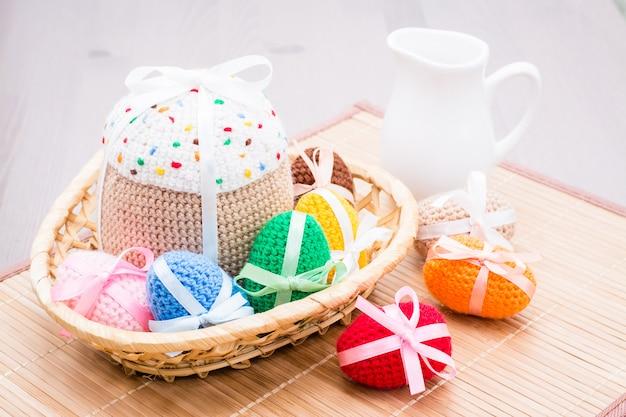 Вязаные пасхальные яйца и торт в корзине на салфетке на столе