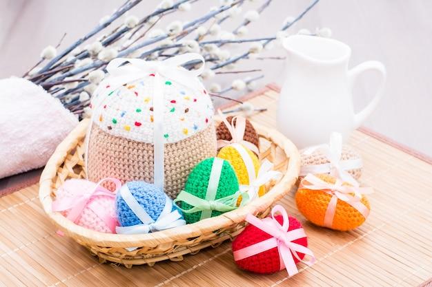Вязаные пасхальные яйца и торт в корзине, кувшин и ива
