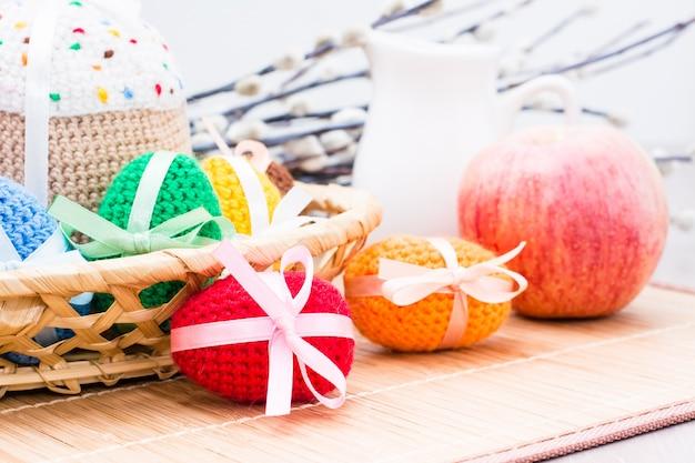 Вязаные пасхальные яйца и торт в корзине, яблоко, кувшин и ива