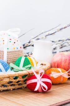 Вязаные пасхальные яйца и кулич в корзине на деревянном столе. пасхальный натюрморт