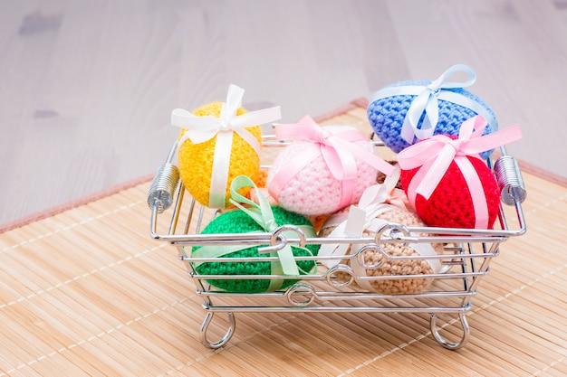 Вязаные пасхальные яйца перевязаны цветными лентами в металлической корзине на деревянном столе