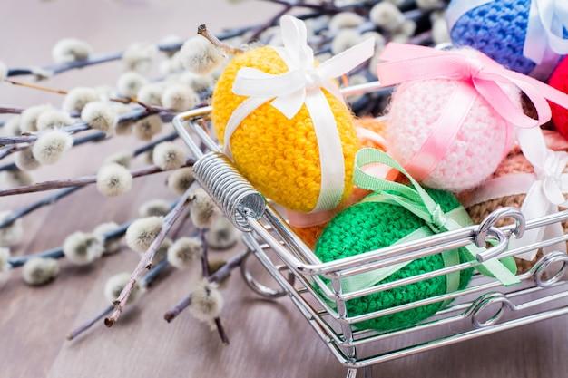 Вязаные пасхальные яйца перевязаны цветными лентами в металлической корзине и ивы на деревянном столе