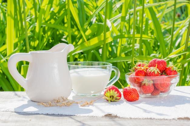 Миска клубники, чашка с молоком и кувшин на столе на салфетке
