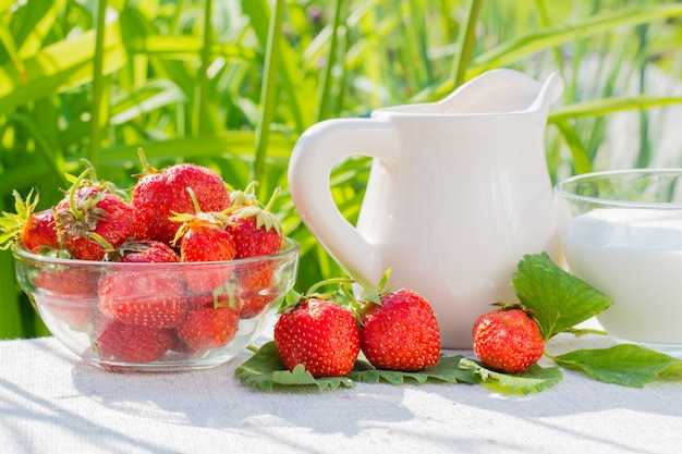 イチゴの果実と葉、水差し、草の背景にナプキンにミルクとカップ