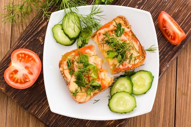 Бутерброды с помидорами, сыром и зеленью и нарезанными овощами. вид сверху