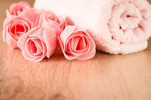 花と木製の背景にタオルの形の石鹸
