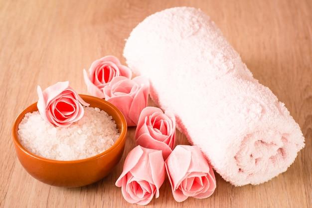 花、海の塩、木製の背景にタオルの形の石鹸