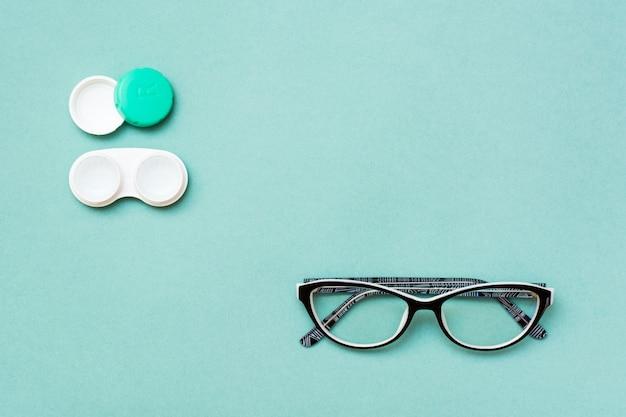 Открытый контейнер с линзами и очками на зеленом фоне