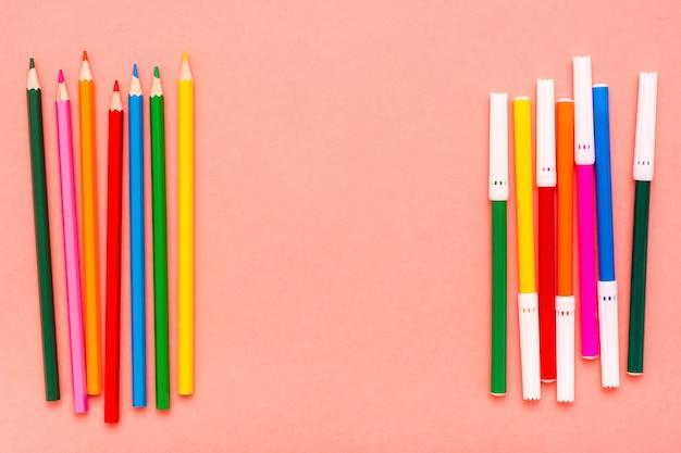 Цветные карандаши и фломастеры на красном фоне