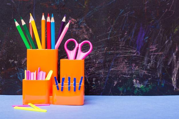 Цветные карандаши, ножницы, счетные палочки и зажимы в стакане для канцелярских товаров