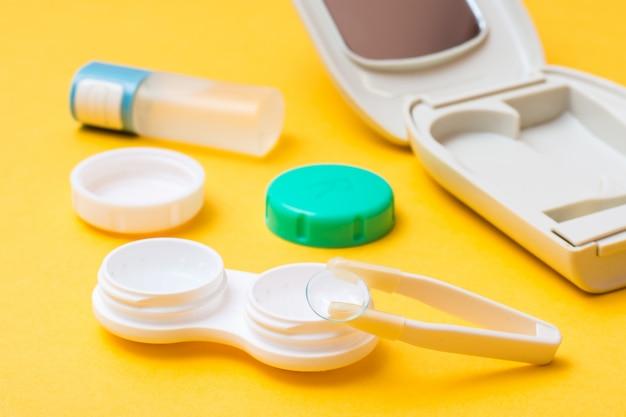黄色の背景にレンズ、ケース、ボトルを保管および清掃するための開いた容器上のピンセット上のコンタクトレンズ
