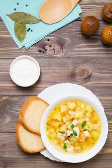 Куриный суп с картофелем и зеленью в белой миске на деревянном столе