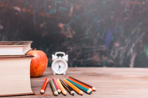 本、鉛筆、時計、黒板に木製のテーブルの上のリンゴと学校に戻る