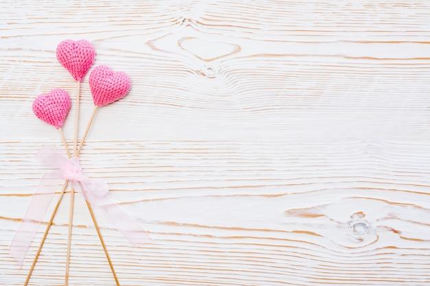 Три розовых вязаных сердца на палочках, перевязанных розовой лентой на белом деревянном