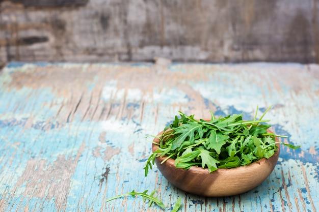 木製のテーブルに木製のボウルにルッコラの新鮮な葉