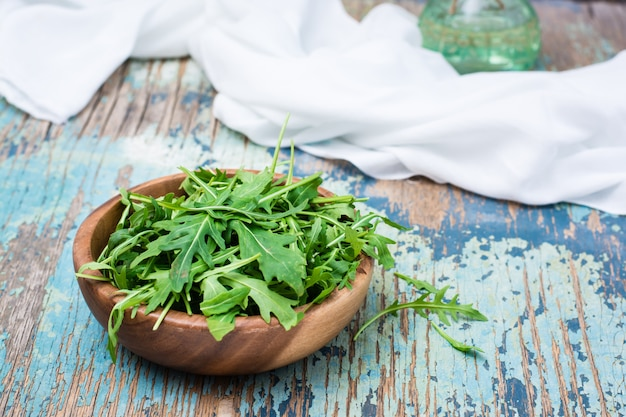 木製ボウルと木製のテーブルに白いナプキンでルッコラの新鮮な葉