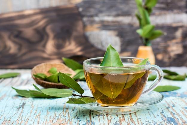 木製の素朴なテーブルの上にカップで月桂樹の葉から新鮮なお茶