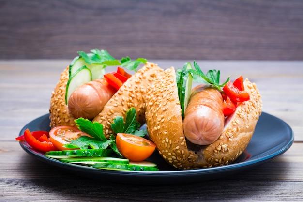 木製テーブルの上の皿に揚げソーセージ、ごまパン、新鮮な野菜から食欲をそそるホットドッグ