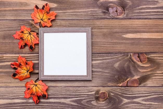 オレンジ色のカエデの葉に囲まれた茶色の木製の背景に準備ができているフォトフレーム。