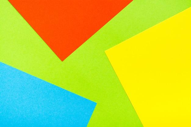 Четыре цвета желтый зеленый красный синий абстрактный картон фона. листы картона укладываются друг на друга. копировать пространство