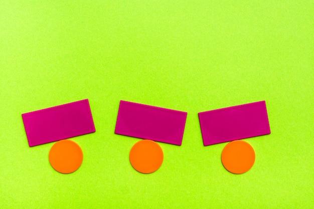 Плоские цветные фигуры - круги и прямоугольники - симулируют балансировку на зеленом картоне. понятие равновесия. копировать пространство