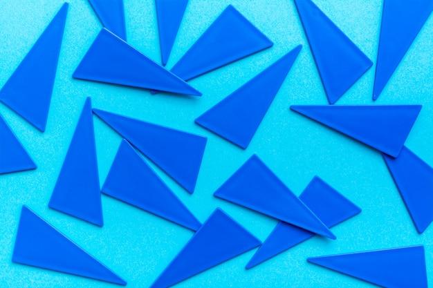 青いプラスチックの平らな三角形は、青色の背景に無秩序に散らばっています。幾何学的なプレーンバックグラウンド。上面図