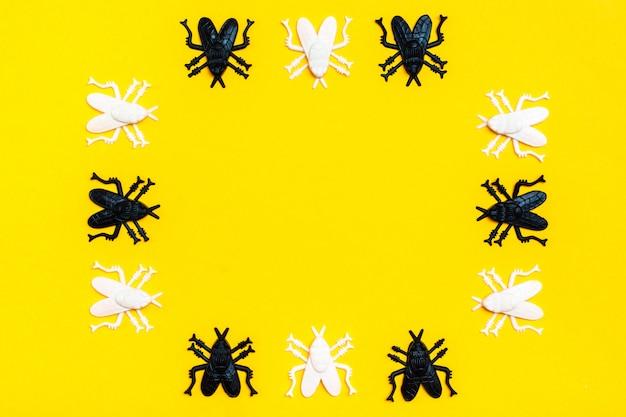白と黒のプラスチックハエは、黄色のフレームの段ボールの背景にフレームを構成します。準備ができているハロウィーンの招待状。コピースペース