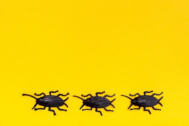 黄色の段ボールの背景に黒いプラスチックゴキブリ。準備ができてハロウィーンのイラスト。コピースペース