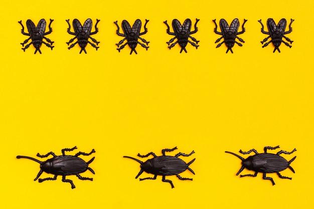 黒いプラスチックのゴキブリと黒いプラスチックが黄色の段ボールの背景に飛ぶ。準備ができてハロウィーンのイラスト。コピースペース