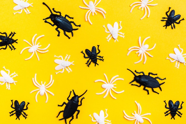 黒と白のプラスチック製のハエとカブトムシは、黄色の段ボールの背景にランダムに横たわっています。ハロウィーンの準備ができて背景。