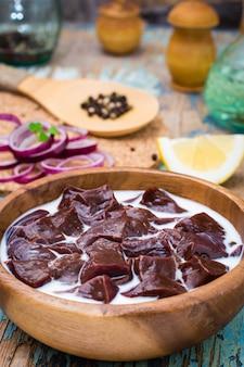 Кусочки сырой говяжьей печени замоченные в молоке в деревянной миске и ингредиенты для приготовления пищи на столе