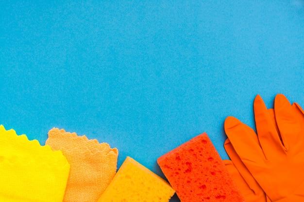 皿、マイクロファイバーのぼろきれ、ゴム手袋を洗うための色の付いたスポンジが青い背景に並んでいます。クリーニングツールの概念。コピースペース