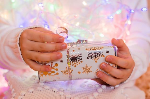 Подарок, завернутый в праздничную упаковку в руках ребенка в белом вязаном свитере на фоне боке гирлянды разных цветов. рождественские приготовления концепции