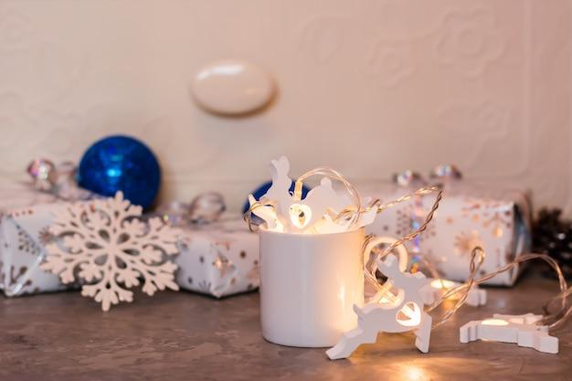 クリスマスの静物。包まれた贈り物の背景に白いカップに鹿とガーランド。