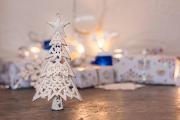 クリスマスの静物。包まれた贈り物やクリスマス用品の背景に輝く装飾モミの木。