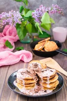 フルーツヨーグルトを詰め、木製のテーブルの皿にすりおろしたチョコレートを振りかけたパンケーキの山