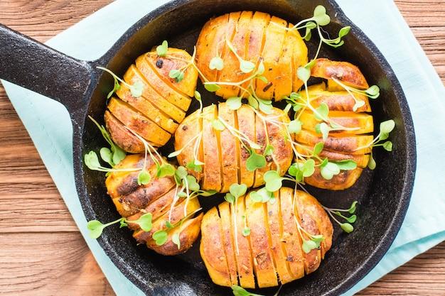 木製テーブルの上の鉄鍋でルッコラとスパイスと油で焼きたての若いジャガイモのクローズアップ。上面図