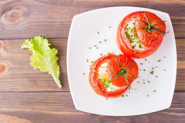 フレッシュトマトはチーズと鶏の卵を皿に焼き、サラダは木製のテーブルに焼きました。上面図。