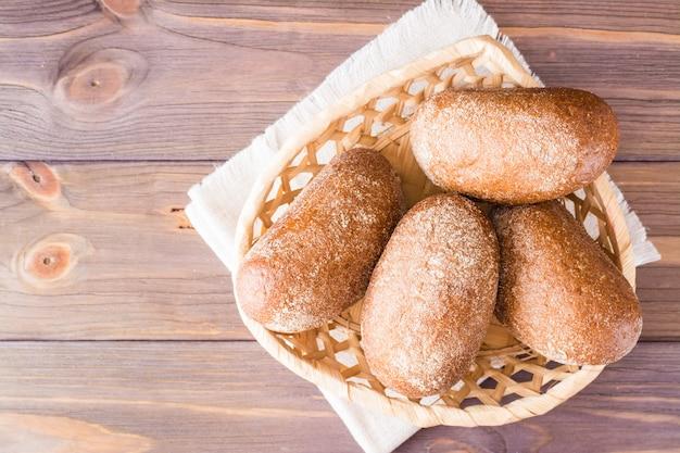木製のテーブル上のバスケットの新鮮なライ麦パン。上面図。コピースペース