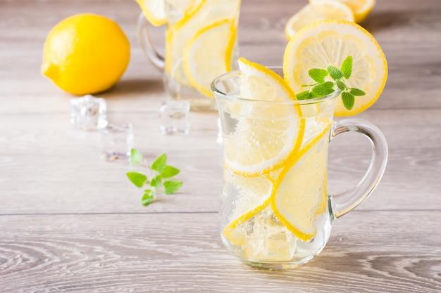 Освежающая холодная минеральная вода с кубиками лимона, мяты и льда в очках на деревянном столе