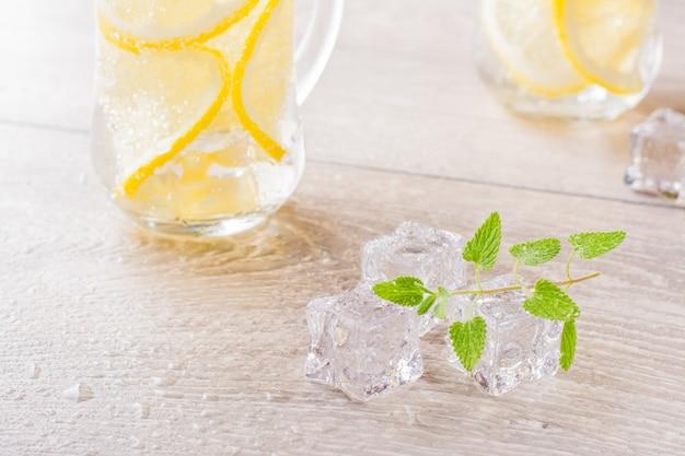 Тающие кубики льда, листья свежей мяты и вода с лимоном в стакане на деревянном столе