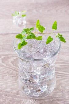 Холодная минеральная вода с кубиками льда и листьями мяты в прозрачном стакане на деревянном столе