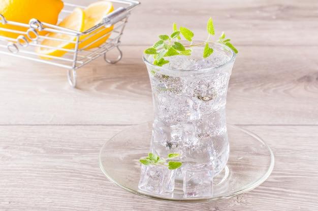 Освежающая минеральная вода с кубиками льда и листьями мяты в прозрачном стакане и лимоном в корзине на деревянном столе